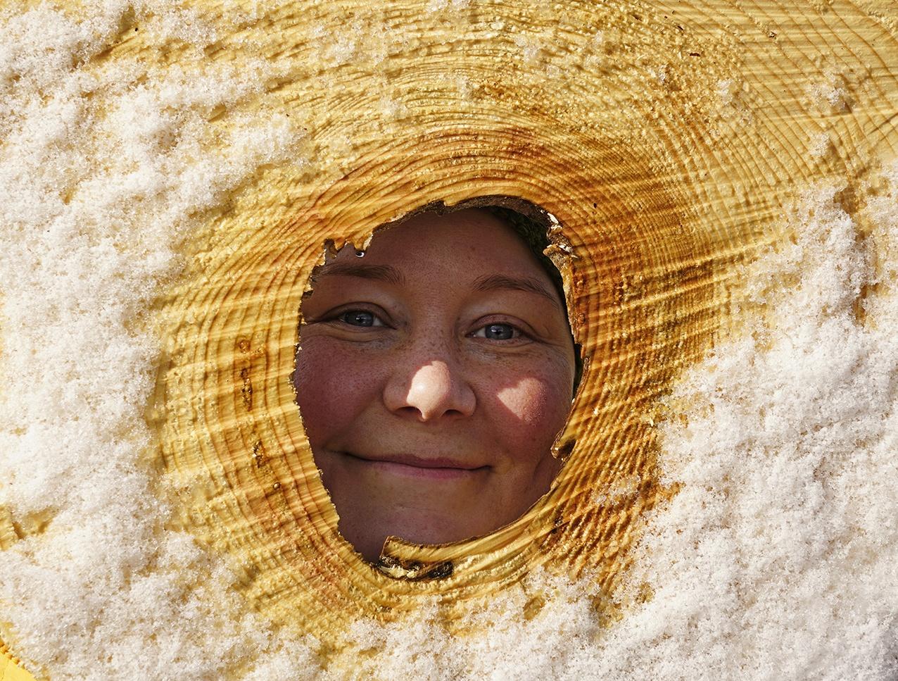 En leende person tittar mot kameran genom en trädstam, Fotograf: Andy Horner