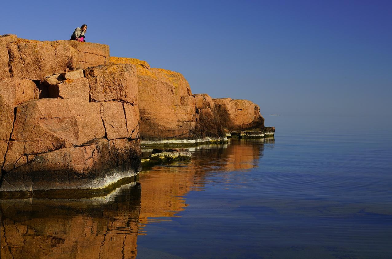 En person sitter på klippor vid vattnet, Fotograf: Andy Horner