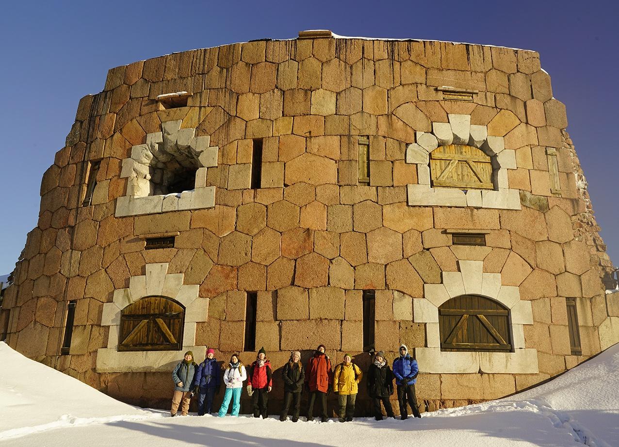 En grupp studerande i friluftskläder står i snön vid en fästning, Fotograf: Andy Horner